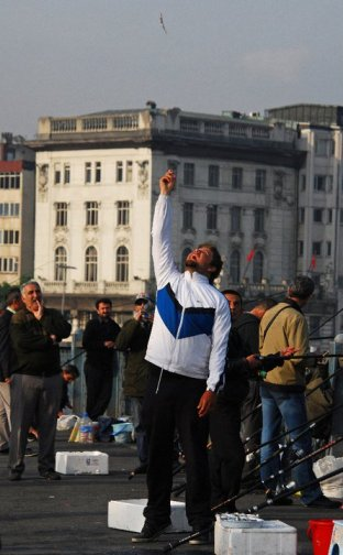Istanbul is full of interesting characters - many of them can be found on Galata Bridge. A fisherman tosses fish in the air for the sport of seagulls. © Desiree Koh